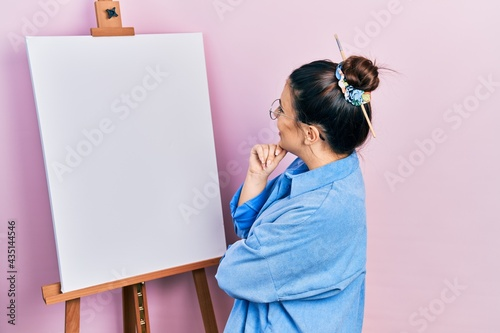 Young beautiful painter woman standing by easel with blank empty canva Fototapet
