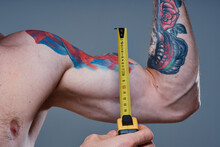 Guy Measures Arm Muscles With Centimeters On A Gray Background And A Multicolored Tattoo Bodybuilder Fitness