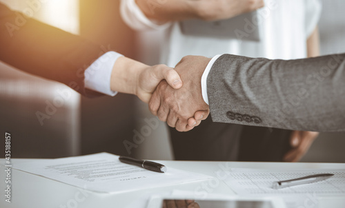 Fotografia Business people shaking hands finishing contract signing in sunny office, close-up