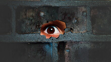Eye Looking Through The Hole On Cracked Wall. Spy Peeking Through Hole In Brick Wall. Spy Concept.