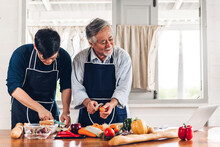 Portrait Of Happy Love Asian Family Senior Mature Father And Young Adult Son Having Fun Cooking Together And Looking For Recipe On Internet With Laptop Computer To Prepare The Yummy Eating Lunch