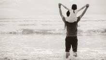 Little Child Girl Riding On Dads Neck. Father And Daughter Standing On Beach. Concept Of Fathers Day And Sepia Color Style