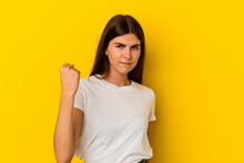 Young Caucasian Woman Isolated On Yellow Background Showing Fist To Camera, Aggressive Facial Expression.