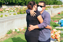 Husband With Protective Mask Trying To Comfort His Wife In A Cemetery. Tragic Results Of The Coronavirus