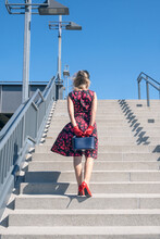 Back Of Blonde Woman In Red Dress Walking Up Stairs Outside