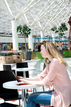 Young Woman Wearing Pink Cardigan Is Using Digital Tablet Sitting At The Table In A Cafe Of A Shopping Mall Or At The Airport. Freelance Work
