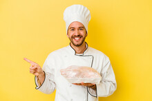 Young Caucasian Chef Man Holding Chicken Isolated On Yellow Background Smiling And Pointing Aside, Showing Something At Blank Space.