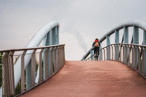 Canvas Print Cyclists on a footbridge in Leverkusen, Germany.