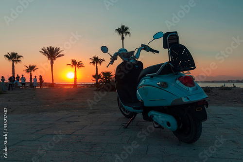 Stampa su Tela A motobike on embankment of sea against the sunset sky on embankment of Side