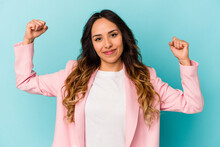 Young Mexican Woman Isolated On Blue Background Showing Strength Gesture With Arms, Symbol Of Feminine Power