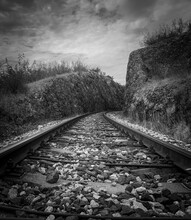 Train Rail Track Into The Distance Leading Between Rocky Hills. Black And White Photo