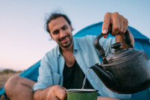 A Young Male Tourist Drinks Tea Near A Tent In The Mountains