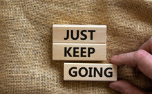 Just Keep Going Symbol. Wooden Blocks With Words 'Just Keep Going'. Beautiful Canvas Background, Businessman Hand. Business, Just Keep Going Concept, Copy Space.