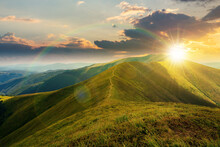 Mountain Landscape In Summer At Sunset. Grassy Meadows On The Hills Rolling In To The Distant Peak Beneath A Rainbow In Evening Light