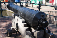 A Cannon Looking Down A Canal In Downtown Amsterdam.
