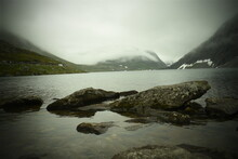 Lake Shore With Stones In The Background Of Snowy Mountains, Mountain Landscape In Gloomy Weather