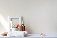 Bathroom Interior In Beige Pastel Tone. White Shelf In Bathroom With Towels, Soap, Perfume Bottle, Hairbrush, Houseplant. Mockup With Space For Text. Minimal Composition.