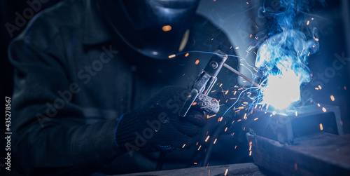 Fotografia Professional welder performs work with metal parts in factory, sparks and electricity