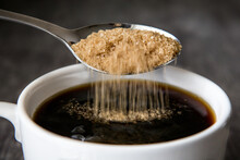 Raw Sugar Being Put Into A Cup Of Coffee