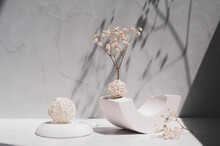 Interior Still Life With Sunlight And Shadows. Gypsum Geometric Shape,  Decorative Balls And Gypsophila Flowers On A Gray Background.