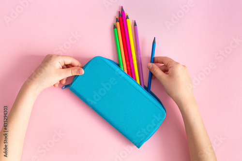 Canvas Print Rainbow multicolored pencils in a blue pencil case in the hands of a child on a pink background