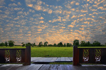 Glisteningly Golden Sky Over Green Field With Wooden Balcony