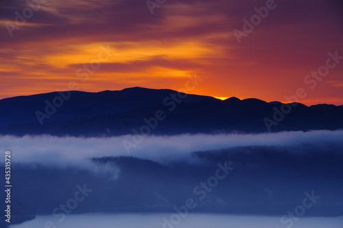 薄い雲のある湖から遠くに見える、山の尾根と夜明けのオレンジ色の空のシルエット。日本の北海道の摩周湖で。 Fototapeta