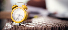 Yellow Alarm Clock In The Foreground, Time Concept.Work From Home.Planning Time Or Wasting Minutes.