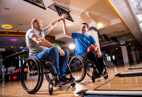 Two young disabled men in wheelchairs playing bowling in the club Tapéta, Fotótapéta