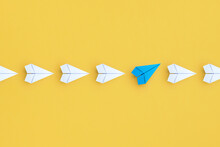Business Concept For New Ideas Creativity And Innovative Solution, Group Of White Paper Plane In One Direction And One Blue Paper Plane Pointing In Different Way On Yellow Background