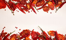 Peppers And Tomatoes Background. Dried Hot Chili Peppers And Red Sun-dried Tomatoes On A White Plate. Spices And Vegetables Food Minimal Flat Lay Background Concept