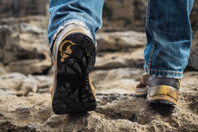 Tourist In Old Worn Out Hiking Boots And Blue Jeans In A Rough Mountain Terrain. Long Journey Concept. Legs In Old Shoes On Hard Stone Surface