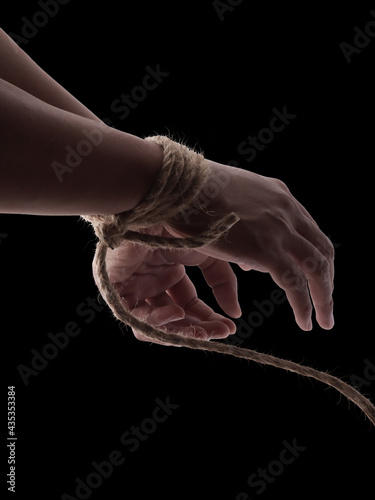 Obraz na plátně Person hands tied with rope isolated on black dark background, captive victim re