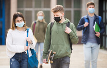 Teen Girl In Protective Face Mask Walking With Her Classmate Outside College Building On Sunny Day