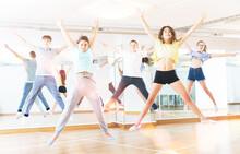 Satisfied Teenage Boys And Girls Jumping Having Fun During Dance Class