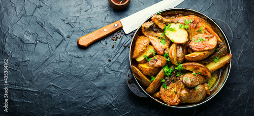 Photo Roast chicken leg with potatoes on iron cast pan