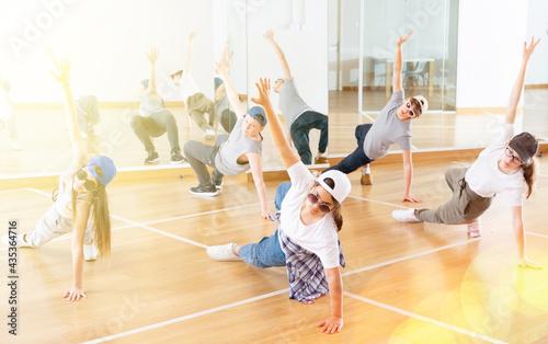 Fotografiet Focused teenage hip hop dancers doing dance workout during group class