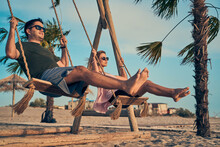Young Attractive Couple Swinging On Seesaw On The Beach.
