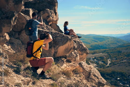 Fototapeta Couple men take a photo woman, who sitting on a rock, looking at the landscape and enjoying the view and fresh air