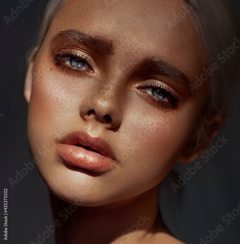Portrait of a girl. Close-up of a woman's face. Freckles on the face. Artistic retouching. Plump lips. Glare in the eyes.