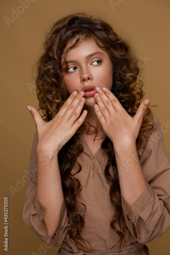 Portrait of a teenage girl. She holds her hands near her face and looks away in surprise. Brown background.