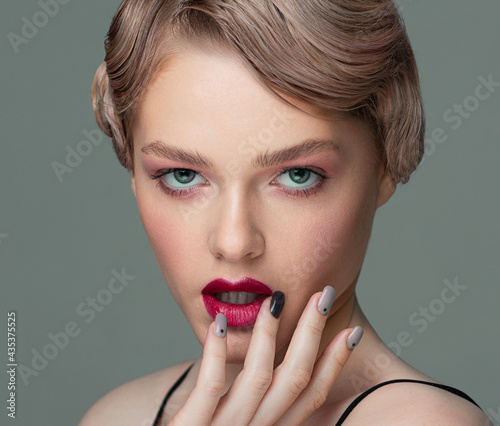 Close-up portrait of a woman. The fingers touch the lips. Well-groomed manicure. Red lipstick. Vintage hairstyle. Retro style.