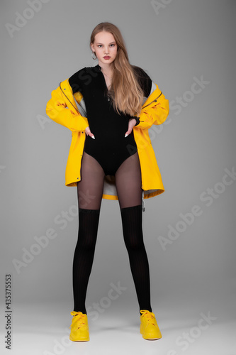Girl in full growth posing in the studio. Clothes - yellow jacket, raincoat. Black claws and yellow sneakers. Fashion & Style.