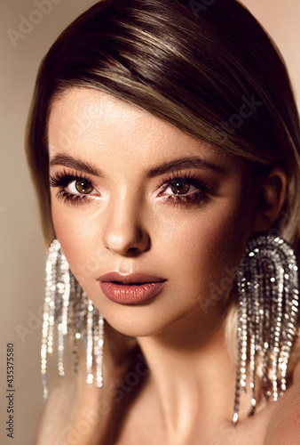 Portrait of a stylish woman. Face close-up. Big earrings. Evening look.