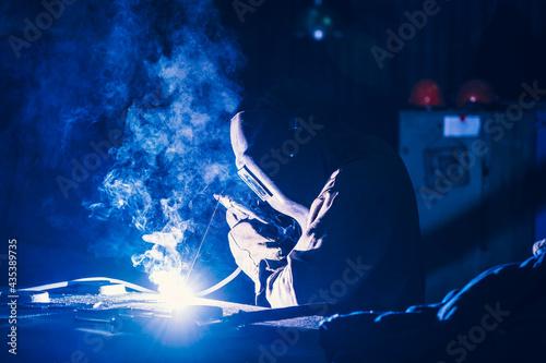 Obraz na plátně Welder in protective mask, sparks and smoke from welding flares, industrial background