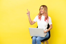 Young Woman Sitting On A Chair With Laptop Over Isolated Yellow Background Pointing Up A Great Idea