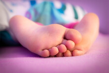 The Feet Of A Baby Sleeping Under The Covers In Bed