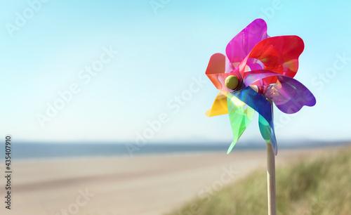 Fotografia, Obraz Summer beach background, pinwheel or windmill in the sand