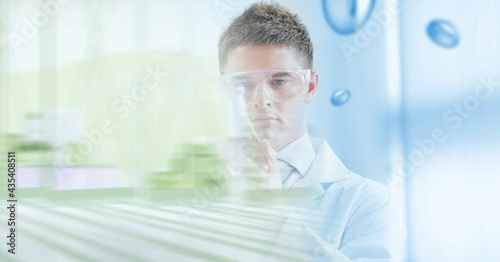 Composition of male scientist holding beaker in laboratory with green motion blur