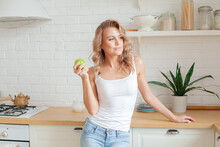 Pretty Young Woman Holding Green Apple And Smiling At Home Kitchen, Diet And Healthy Eating Concept